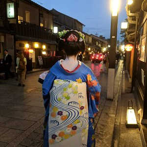 A maiko walking the streets of old Gion at dusk