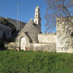 il bel campanile della chiesa dietro ad un trullo in primo piano