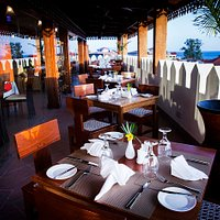 Restaurant out door view overlooking the Indian ocean with glass panorama for indoor air conditioning  seating.