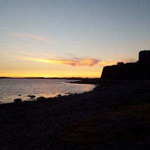 Solnedgång över Getterön med Fästningens silhuett i högerkanten. Bilden tagen från Strandpromenaden.