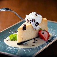 White Chocolate Cheesecake Italian style, rich white chocolate, espresso creme anglais, whipped cream.