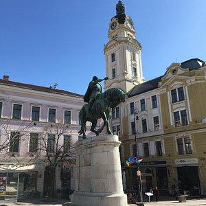 Schöne Gebäude und im Vordergrund die Statue von Hunyadi Jànos