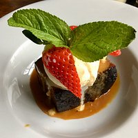 Sticky Toffee Pudding served with ice cream and caramel sauce with a garnish of strawberry and mint.    The best desert to be found in the Winchester area, but beware, it is very filling!