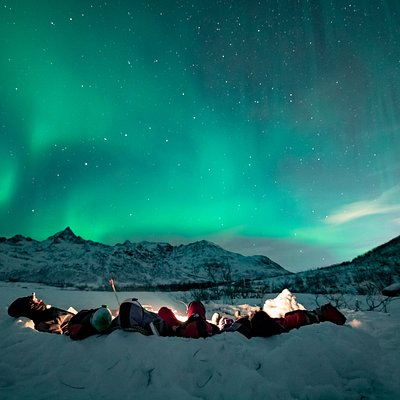 Travellers comfortably settled on a temporary snow camp, facing the bonfire ,with a hot and home-made soup in their hands, mesmerised by the Northern Lights.