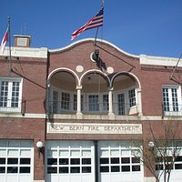 Outside shot of the firehouse with the New Bern symbol (the bear) just below the flag.