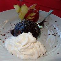 Fondant au chocolat accompagné de chantilly et d'un signe découpé dans une pomme . Un dressage soigné !!!