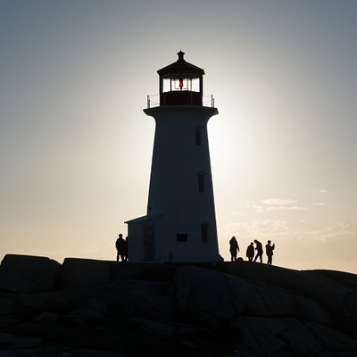 Peggy's Cove lighthouse bathed in golden hour light on our Sunset Photo Tours.