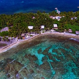Aerial View of Off The Wall Dive Center and Resort, located on Long Caye, Glover's Reef Atoll, in Belize. About 37 miles off shore. Pristine reef accessible by walk in snorkeling, or by a 2 minute boat ride to world class diving and famous dive site, rated by Jacques Cousteau as one of his top 10 dives of his life. No crowds, healthy reef, abundant and colorful sea life.