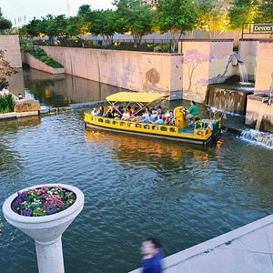 A Water Taxi turning around in the Bricktown Canal's western terminus, in front of the Devon Mosaic.