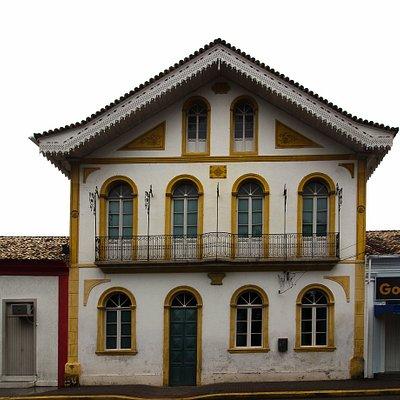 Vista frontal do prédio e seus belos rendados no telhado.