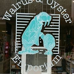 Front window of the shop showing Emma Davis' artwork of the Walrus (in his Doc Martin boots) with an oyster