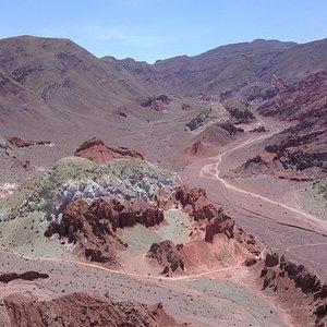 valle del arcoíris Ubicada al oeste de la Cuenca del Salar de Atacama, la Cordillera de Domeyko posee uno de los paisajes más enigmáticos e interesantes de observar, el Valle del Arcoiris donde la gran variedad de rocas se refleja en un abanico de colores. Además la biodiversidad existente en esta zona ha hecho posible la existencia del hombre atácameño evidenciada en el arte rupestre.