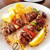 BBQ tender lamb chunks on a skewer with peppers and onions, potatoes