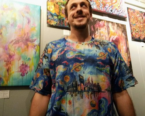 Another satisfied customer wearing featured artist Elaine Alonzo t-shirt in front of her artwork