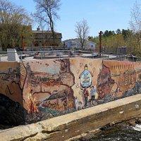 Fresque du Peuple Wendat sur le mur bordant la place Onywahtehretsih et la rivière Akiawenrahk juste avant que celle-ci ne se jette dans les Chutes Kabir Kouba.