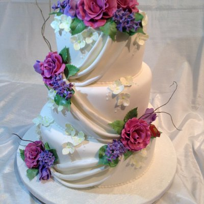 Elegant wedding cake featuring all edible flowers and curly willow.