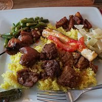 Variety on the plate - beef, pork, chicken, vegetables, white and saffron rice.