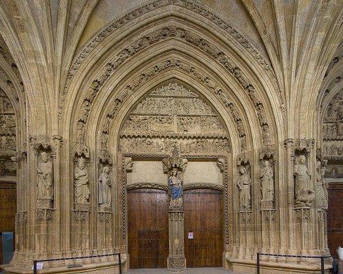 El precioso pórtico: El portal central se relata la vida de la Virgen. El registro central trata de la Ascensión, Pentecostés, el viaje de los apóstoles y la muerte de María y se remata con la escena de la coronación de la Virgen por su Hijo. El tímpano de este portal está ocupado por una imagen de la Virgen con el Hijo del siglo XV.  El portal derecho muestra el juicio final. Se puede observar a San Miguel pesando las almas, las que se dirigen, bien en la puerta de la Gloria o en el infierno.
