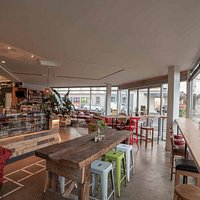 The front section of the café with communal table and standing benches - wifi available