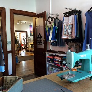 onewomanstudio is a retail space and working studio. Shown here is one of the vintage sewing machines I use daily, and some of the upcycled clothing I make and sell.