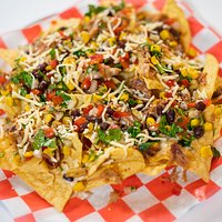 Corn chips heaped high with pulled pork, black beans, corn, avocado, sweet onions, red bell & poblano peppers, pickled jalapeno & topped with white cheddar queso.