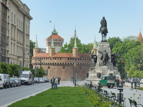 In the background, Saint Florian's Gate , then the Kraków Barbican (Barbakan Krakowski), and the Grunwald Monument