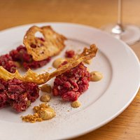 Battuta al coltello condita con capperi, cipolla rossa, peperoni, cetriolini e salsa Tartara