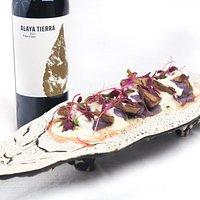 Presa ibérica con puré de patata violeta, trufa rallada, salsa de queso manchego y humo de roble.
