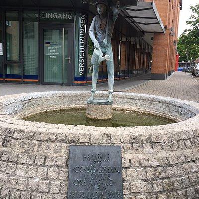 """Der Hamballe ist der """"Urtyp hochgeistiger Einfalt"""". 1986 wurde diese Figur, die einen Mann mit Regenschirm zeigt der gerade Blumen gießt, in der Bahnhofstraße als Brunnenfigur aufgestellt. Bildhauerisch gestaltet wurde der Hamballe von Hermann Koziol. Umgangssprachlich ist jeder ein Hamballe, der in Öhringen geboren wurde."""