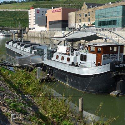 Kunstschiff ARTE NOAH im Alten Hafen hinter dem Kulturspeicher. Zu Fuß: Nehmen Sie den Fußweg von der Schiffsanlegestelle / vom Alten Kranen flussab zehn Minuten: Geheimtipp!