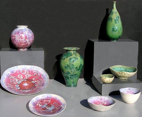 Vue d'ensemble de quelques coupes et vases en porcelaine avec émail cristallisé fuchsia ou vert émeraude