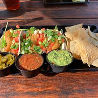 Battered perch tacos with a side of jalapenos and guacamole. The chips and salsa are included.