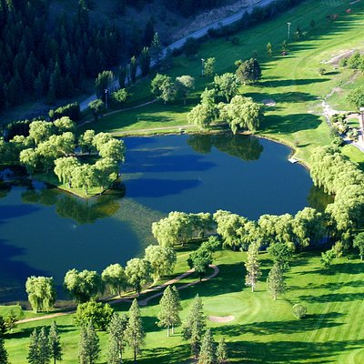 Aerial view of St. Andrews By-The-Lake golf course with lake and island green. The Clubhouse is to the right.