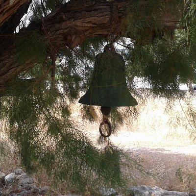 The bell of Agios Georgios hanging in a tree near the Church