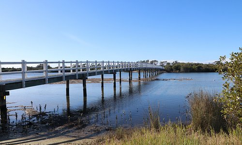 Opposite the entrance to the Holiday Park. The footbridge provides access to the beach - an easy 10 minute walk through bushland and sandunes.