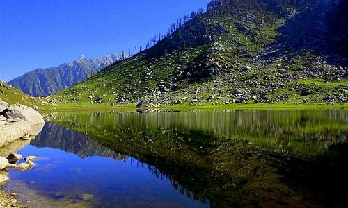 Clear weather; A place with Picturesque view. peaceful valley of snow with white water lake;