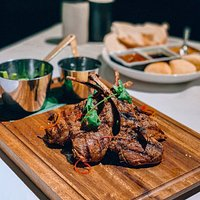 Harissa spiced lamb cutlets - Australian lamb cutlets rubbed with Harissa spices and barbequed,served with orange and pistachio couscous, buttered snow peas, chermoula dressing.