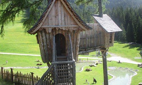 """Parco gratuito """"Villaggio degli gnomi"""" sopra il Monte Baranci, San Candido, una delle casette di legno, e in basso le piscine del Gigante"""