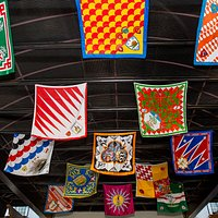 The Contrada (Neighborhood) flags of Siena, Italy fly above the entrance to Il Palio