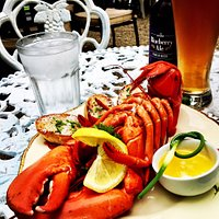 Acadian-style lobster served with garlic butter, garlic bread, lemon, and a cold beer.