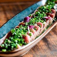 Nosso clássico Tataki de Atum Açoreano, braseado, mal passado, em fatias temperadas com molho teriaky, sementes crocantesde sésamo e cebolinho