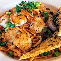 Our Seafood Linguine- Sauteed scallops, shrimp, and red onions over linguine with white wine and rosa sauce. Topped with green onions. Served with garlic bread