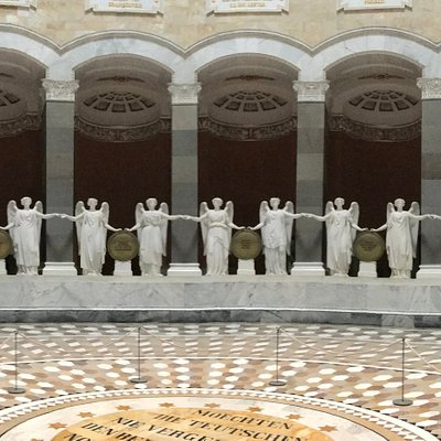 34 monumental goddesses of Victory in white Carrera marble join hands in a ceremonious round dance.