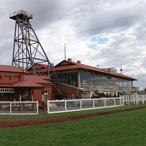 Inland horse racing  Kalgoorlie Boulder Western Australia. View from the turf level, grandstand or on course screens, the race horse parade ring - mounting yard, currently winners presentation area. Industry area, stewards, racing personal, jockey's. View to public and members areas, hardstand and grass areas underfoot for pedestrians.