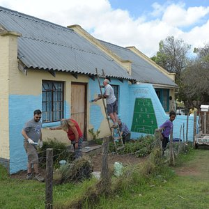 Huisjes van de bevolking geschilderd in vrolijke kleuren, sommige met historische referenties naar de eerste bewoners van Zuid-Afrika