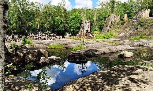 """Ekomuseum Nedre Ätradalen  Döda fallet heißt """"Toter Wasserfall"""". Es handelt sich hier um eine altes Wasserkraftwerk aus dem Jahre 1907 Reste der alten Staumauer sind noch zu sehen. 18,5 Meter stürzte das Wasser in die Tiefe und erzeugte so mittels erst 3, später 4 Turbinen den Strom – bis 1964. Dann baute man 1,5 km flussaufwärts eine neue Anlage. Über die blank geschliffenen Steinplatten kann man heute laufen und das alte Flussbett erkunden."""