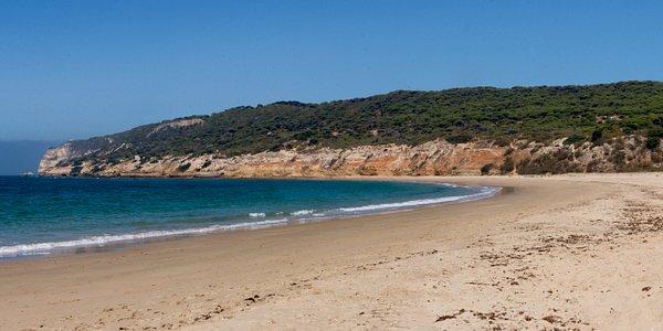 Vista panorámica de la playa con los acantilados del Parque Natural de la Breña al fondo.