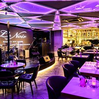 Inside of Le Noir offers upscale dining in a warm and inviting ambience with daily live entertainment