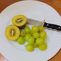 Yellow kiwi fruit and green grapes