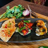 Mix tapas platter consists of Masala papadam, Chicken 65 and tandoori shrimp.